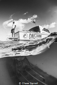 """""""Lookout"""" A dive master stands on the swim platform of a... by Chase Darnell"""