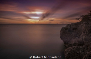 Dive Site Oil Slick in Bonaire just after sunset. by Robert Michaelson