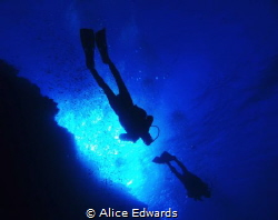 My dive group above me with sun rays at big brother islan... by Alice Edwards