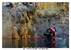 Diver at the surface in the cavern section of a flooded m... by Michael Grebler