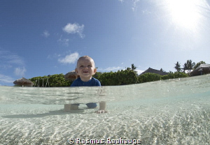 My little boy playing in the water in the Maldives by Rasmus Raahauge