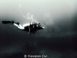 Nice diver with a wreck as background by Xiaoqian Cui