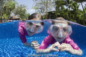Kids playing in pool. by Petteri Viljakainen