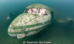 Diver examines a Plane wreck. Cockpit lit with off camera... by Spencer Burrows
