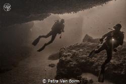 2 divers exploring an overhang by Petra Van Borm