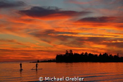 A couple share a quiet evening on stand-up paddle boards ... by Michael Grebler