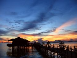 Sunset over cosy water chalets of Kapalai. Waves for song... by Lillian Khoo