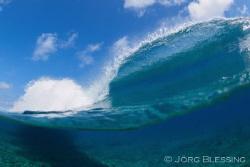 Wave breaking over reef by Joerg Blessing