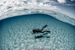 Overunder shot. Diver on a white sandy ocean floor. by Lorenzo Mittiga
