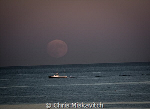 Thatcher Island at dusk.....A Lobsta boat heads back to port by Chris Miskavitch