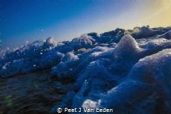 The last rays of  sunset transformed into a rainbow by Peet J Van Eeden