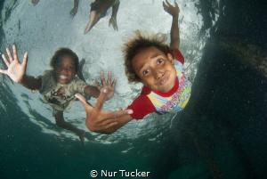 Local children of the Arborek Jetty by Nur Tucker