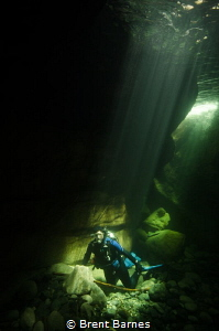 A diver under sun rays through the crystal clear waters o... by Brent Barnes