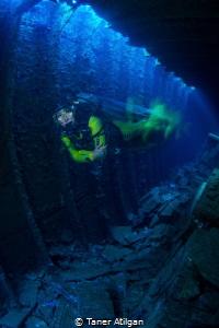 Speeding diver inside the wreck - long exposure by Taner Atilgan
