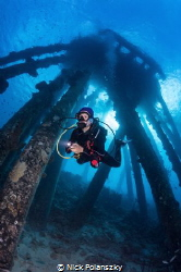Scuba diver Natalia checking out the obscure structures o... by Nick Polanszky