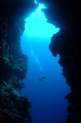 Diver swims past cave entrance, Bunaken National Park.