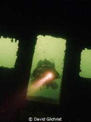 Diver prepares to enter sunken boat. by David Gilchrist