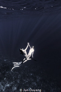 2 divers dancing in the deep by Jun Ouyang