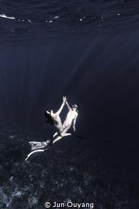 2 divers dancing in the deep by Jun Ouyang