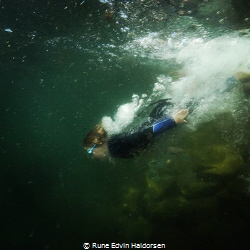 A boy is diving into the cold water of the west coast of ... by Rune Edvin Haldorsen