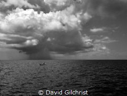 Honduran fisherman on the  waters off Roatan as storm app... by David Gilchrist