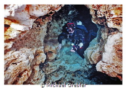 Cave diver passing through the keyhole rock formation in ... by Michael Grebler