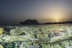 Red Sea at sun set- an over under shot of our live aboard... by Nur Tucker