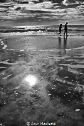A day at the beach. People walking the surf line at Myrtl... by Arun Madisetti