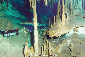 divers lighting the beauty of the Dreamgate cave, Riviera... by Antonio Venturelli