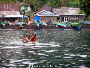 Children of Tandurusa Village playing on a makeshift raft... by Pauline Walsh Jacobson