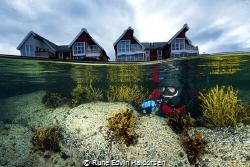 A diver in front of some houses in Vesterålen, Norway by Rune Edvin Haldorsen