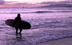 All in a Day's Work. Image of surf instructor at sunset, ... by Glenn Poulain