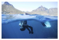 A freediver prepares to dive off Cape Town, with Lion's H... by Roger Horrocks