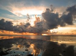 Squall at sunrise, Kosrae. by George Mcguire