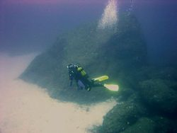 Diving off Cirkewwa reef, Malta,with 'sugar loaf'rock in ... by Ian Palmer
