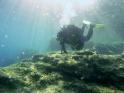 Diver starting the dive on Cirkewwa reef with the suns ra... by Ian Palmer