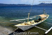 Dive boat with a sleeping boatman on a surface interval. by Gurney Fermin