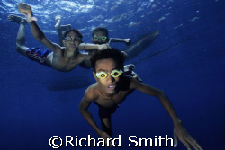 Children swimming down from their canoes with homemade co... by Richard Smith