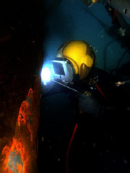 Hot work  ...US Navy diver welds a plate on the bow of a ... by Andrew Mckaskle
