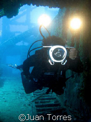 Videographer (Tito) inside the wreck of the WIT Shoal in ... by Juan Torres