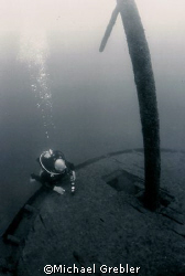 A diver checks his gauges at the stern of the Rothesay wh... by Michael Grebler