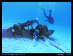 2 divers with a plane wreck in Jamaica. by Margo Cavis