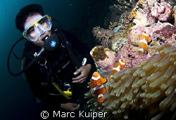 diveguide as model in front of anemone with western clown... by Marc Kuiper