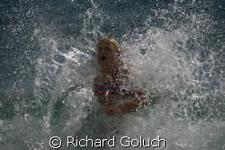 Splashing in water of the coast of Kauai after a dive. by Richard Goluch