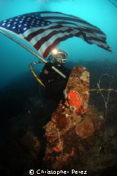 US NAVY DIVER WAVES AMERICAN FLAG OVER A WORLD WAR 2 AERI... by Christopher Perez