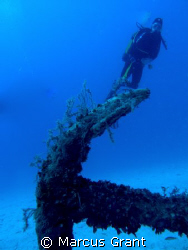 A diver hovers over a large anchor by Marcus Grant