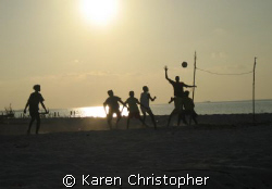 """Young boys play volleyball with a makeshift """"net"""" after t... by Karen Christopher"""