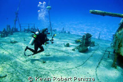 Wendy taking pix of the Shipwreck Tibbits in Cayman Brac.... by Kevin Robert Panizza