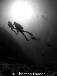 divers at Landaa Giraavaru by Christian Loader