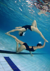 Connected. Synchro swimmers in a pool. by Alena Vorackova